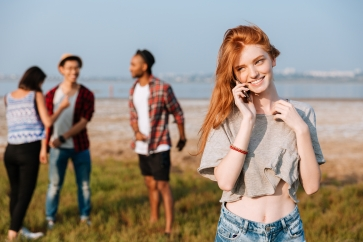 Cheerful woman talking on cell phone standing near her friends